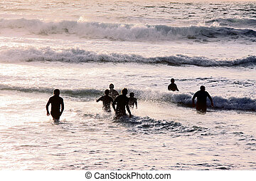 Swimmers in the sea - A group of swimmers / surfers running...