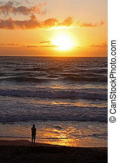 Lady on beach watching an ocean sunset - A lady on the beach...
