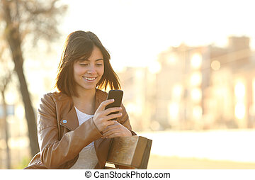 Happy girl using a smart phone in a city park sitting on a...