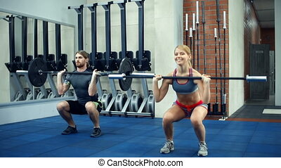 Gym Companions - Close up of two athletes in a gym doing...