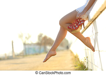 Woman legs silhouette with heels hanging of her hands -...