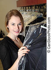 Woman in  Dry Cleaning with clothes packed in plastic foil