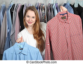Employee of a dry cleaning presenting two clean shirts