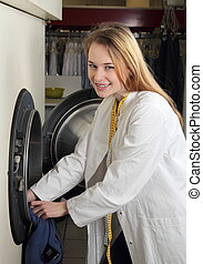 Employee of dry cleaning loads a professionial washing machine