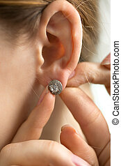 Macro shot of young woman trying on diamond earring - Macro...