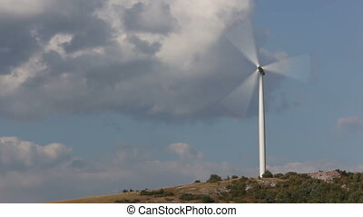 Wind turbine against sky with clouds Mediterranean landscape...