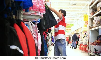 Young man chooses clothes in shop, trying on a jacket HD...