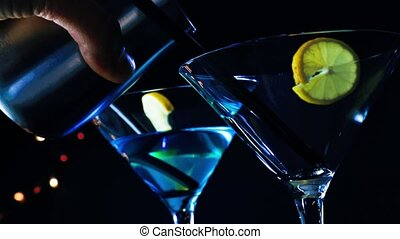 blue and yellow cocktail drink - barman pouring blue and...