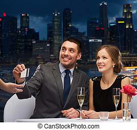 smiling couple paying for dinner with credit card -...