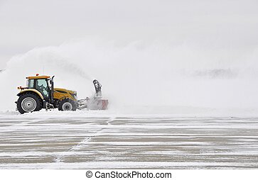 Snow removal - large tractor with snow plow at work during a...