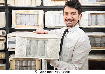 Mattress - The young salesman is showing quality mattresses...