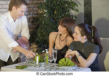 flirting with waiter - two woman flirting with waiter in a...