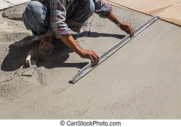 Construction worker spreading wet concrete on the ground