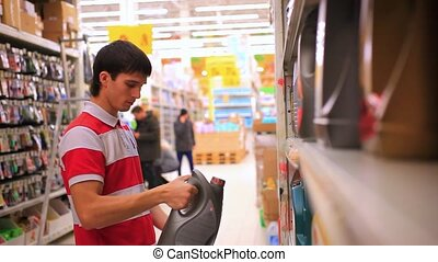 Man chooses and buys automobile chemicals in the auto parts...