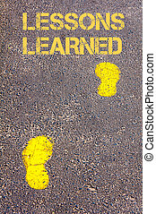 Yellow footsteps on sidewalk towards Lessons Learned...