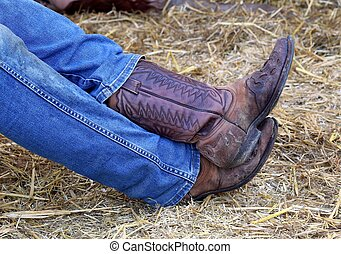 Cowboy leather boots with a pair of jeans in the stable -...