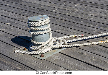 Mooring rope - Bollard with mooring rope on wooden quay in a...