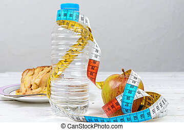 bottle of water and an apple with a measuring tape