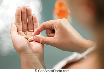 Young woman taking vitamins ginseng pill - Close up view of...