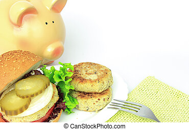 Vegan sea patties and burger on plate with piggy bank...