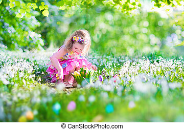 Little girl at Easter egg hunt - Adorable curly toddler girl...