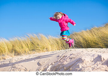 Little girl jumping in sand dunes - Happy funny little girl,...