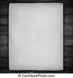 vintage sheet of white paper with rough edges on black...