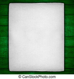 vintage white sheet of paper with rough edges on green...