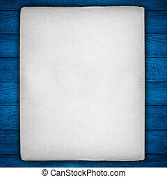 vintage white sheet of paper with rough edges on blue wooden...