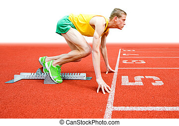 Runner at Starting Block - A young male runner crouches in...