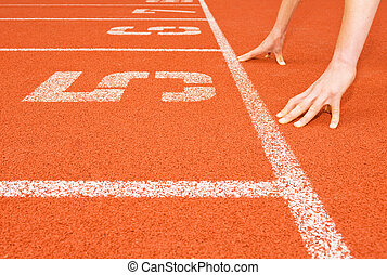 Runner\'s Hands at the Starting Line - A runner crouches in...