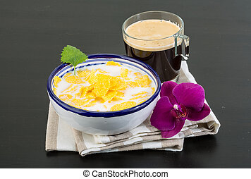 Cornflakes - Breakfast with sweet cornflakes and milk on the...