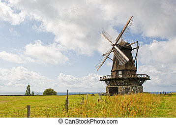 Windmill in a Field - An old windmill is shown in a rural...