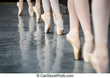 Legs dancers on pointe, near the choreographic training...