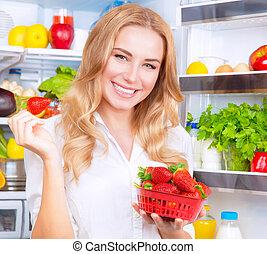 Beautiful woman eating strawberry - Closeup portrait of a...