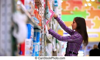 Young woman is shopping in supermarket. She chooses her baby diapers In store. HD. 1920x1080