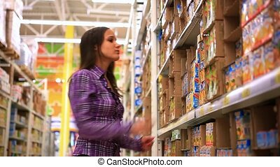 Young woman is choosing food for her child in shopping...