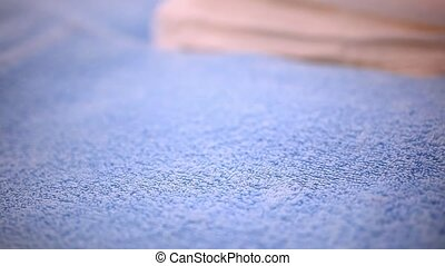 Close-up of woman putting fresh clean towel on bed and then smoothing it with her hands. HD. 1920x1080