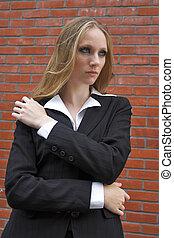 strict schoolteacher standing near a red brick wall