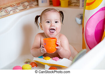 funny baby smiling while taking a bath - funny toddler girl...