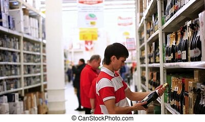 Young man is shopping in supermarket Choosing bottle of...