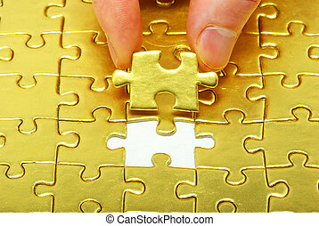 gold puzzle - woman fingers holdings gold puzzle