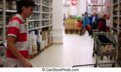Man with trolley checking shopping list at supermarket. HD. 1920x1080