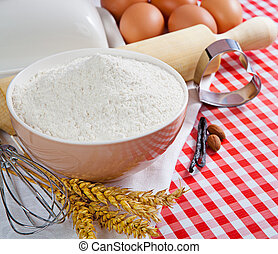 Flour and ingredients for baking in the red checkered...