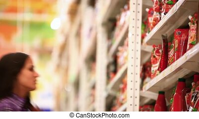 Young woman is shopping in supermarket. Choosing ketchup or tomato paste In the shop. HD. 1920x1080