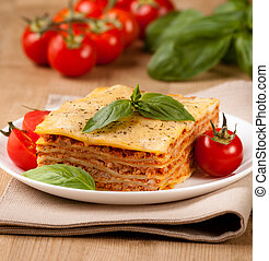 Tasty flavorful lasagna on a plate and ingredients - Tasty...