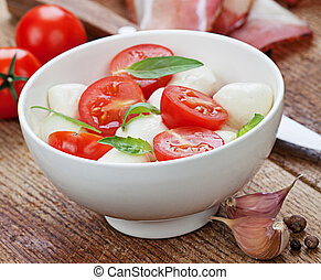 Caprese salad with mozzarella, tomato, basil on white plate