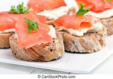 Sandwiches with salmon on white plate, close up view