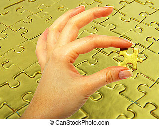 gold puzzle - woman fingers holdings gold puzzle on
