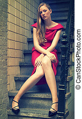 Cross-processed portrait of a pretty fashion model in red...
